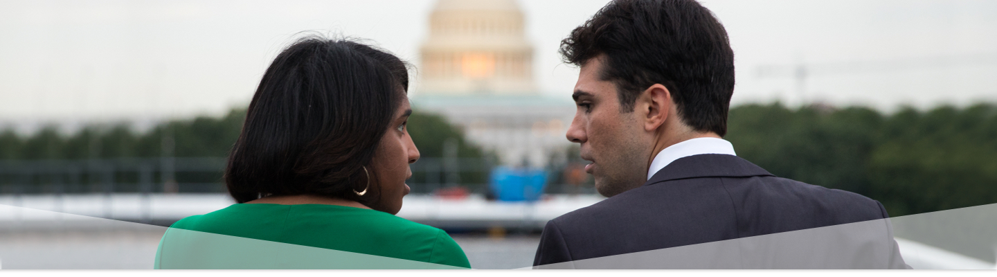 Male & Female GW students talking in front of the Capitol Building