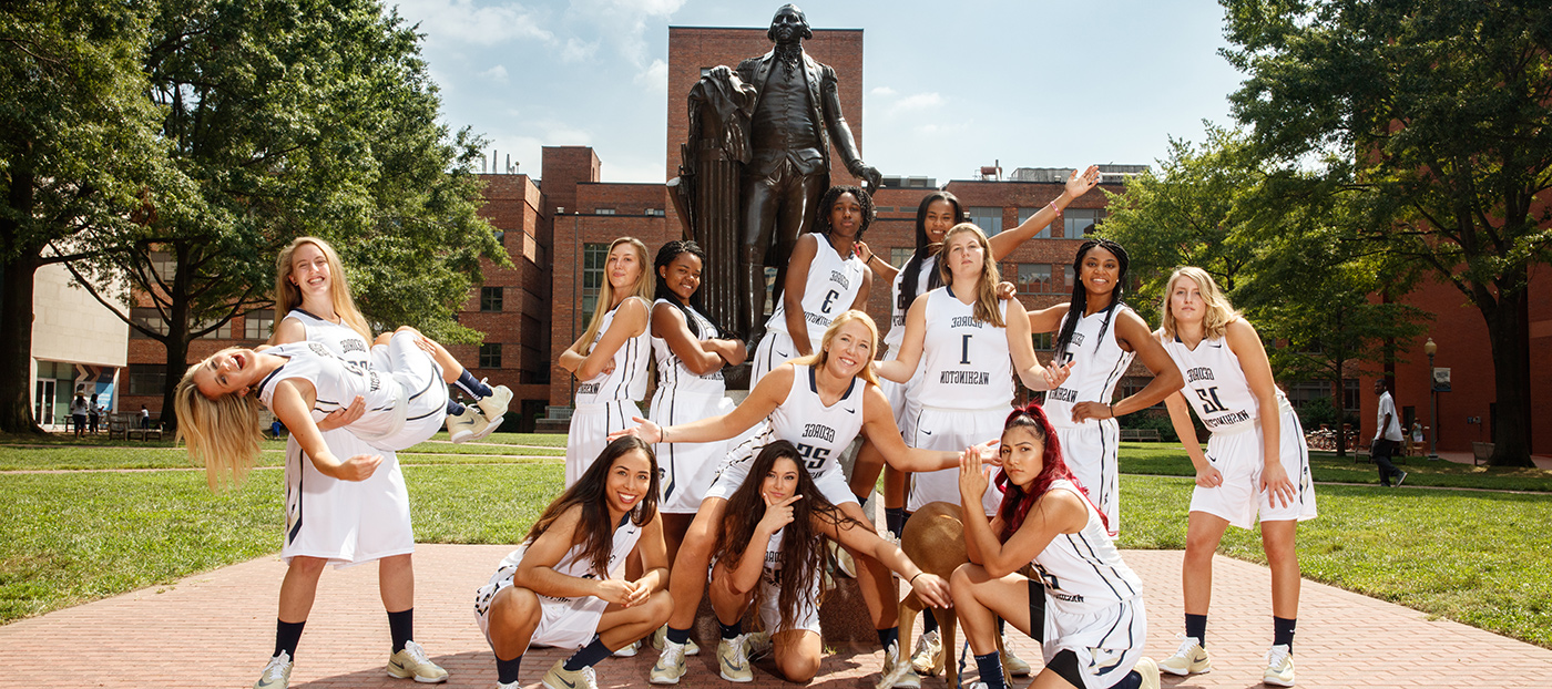 GW Women's Basketball team members pose with George statue in University Yard